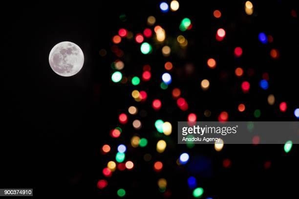The first supermoon of 2018 rises behind the National Christmas Tree in Washington USA on January 1 2018 Supermoons happen when a full moon...