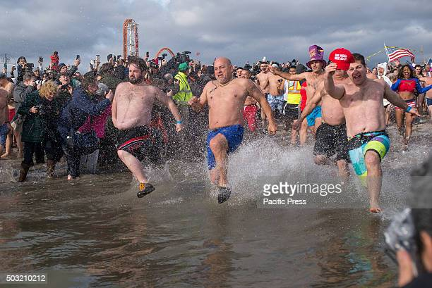 The first swimmers of the Polar Bear Plunge race into the water Over 2500 participants braved the cold on New Year's Day to take part in the 113th...