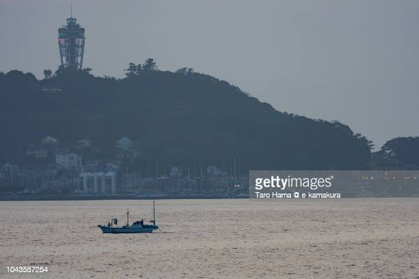 The fisher boat sailing on Sagami Bay and Enoshima Island in Fujisawa city in Japan in the sunset