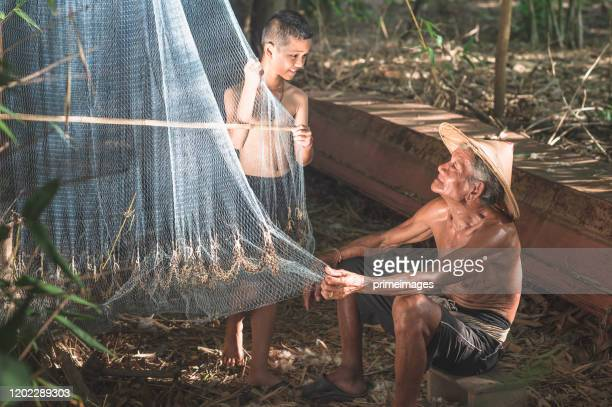 the fishermen are get the fish in the fishing net at nongkhai thailand - primeimages stock pictures, royalty-free photos & images