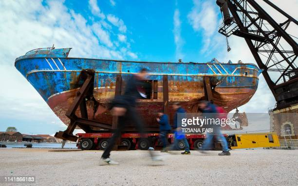The fishing vessel Barca Nostra that sank on April 18 2015 trapping hundreds of migrants in its hull is being installed in Venice's former shipyards...