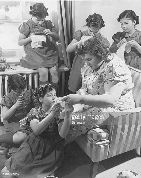 The Five Are Ten Like any other girls of 10 the Quints are fascinated by embroidery Cecile is being straightened out by Mrs Dionne while Yvonne...