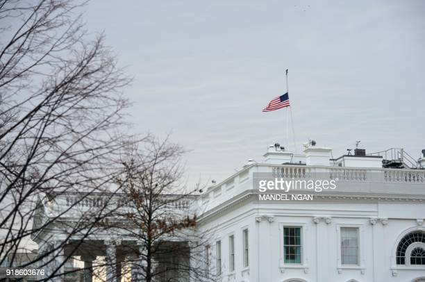 The flag above the White House flies at half staff after an order by US President Donald Trump on February 15 2018 in Washington DC President Donald...