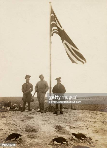 The flag at Cape Adare The two men with distinctive headgear are the two Lapps who accompanied Carsten Borchgrevinck's expedition Antarctica 1898...
