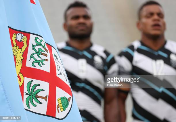 The flag of Fiji is seen as players of Team Fiji sing the national anthem before the Rugby Sevens Men's Gold Medal match between New Zealand and Fiji...