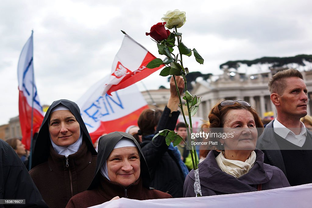 The flag of Poland is held and flowers as crowds watch as Pope Francis appears in the window of his private residence in St Peter's Square to give his first Angelus blessing on March 17, 2013 in Vatican City, Vatican. The Vatican is preparing for the inauguration of Pope Francis on March 19, 2013 in St Peter's Square.