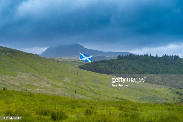 The Flag of Scotland, called The Saltire or Saint Andrew's Cross, flying from a flagpole in typical Scottish landscape, Isle of Arran.