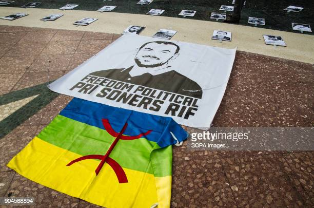 The flag of the Amazigh people beside a banner in memory of political prisoners of the Rif Third March in Barcelona by the resistance freedom and...