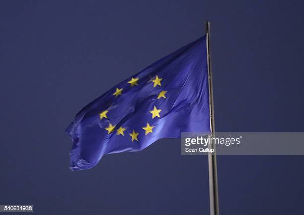 The flag of the European Union flies over the Reichstag at night on June 12 2016 in Berlin Germany Great Britain is scheduled to hold a referendum on...