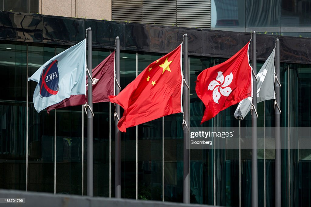 The flag of the Hong Kong Exchanges & Clearing Ltd. (HKEx), left, flies along with flags of People's Republic of China, center, and Hong Kong Special Administrative Region, outside Exchange Square 1 and 2, home of the HKEx, in the Central district in Hong Kong, China, on Wednesday, Aug. 12 2015. Hong Kong Exchanges headed for its steepest slide in two weeks after the bourse operator's profit missed estimates. Photographer: Jerome Favre/Bloomberg via Getty Images
