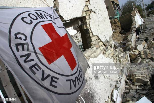 The flag of the International Committee of the Red Cross is seen 28 October 2003 on the rubble of the ICRC headquarters in Baghdad which was attacked...