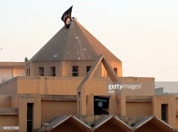 The flag of the Islamic State of Iraq and the Levant flutters on the 'dome' of the Armenian Catholic Church of the Martyrs in the northern rebelheld...