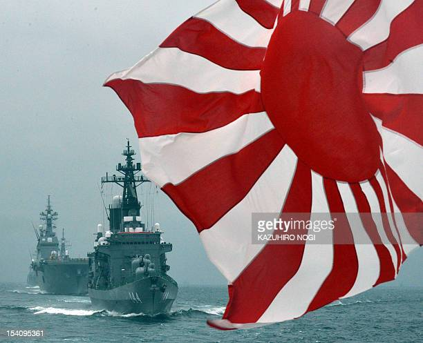 The flag of the Japanese Maritime Self-Defense Force flutters in the wind while MSDF escorts ship Kurama and Hyuga make its fleet review off Sagami...