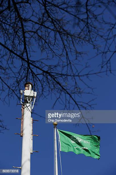 The flag of the Kingdom of Saudi Arabia flys next to a polemounted security camera at its embassy in the United States January 4 2016 in Washington...