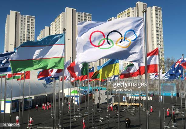 The flag of the Olympic Games is hoisted with national flags in the officially opened athletes' village for the Pyeongchang Winter Olympics in...