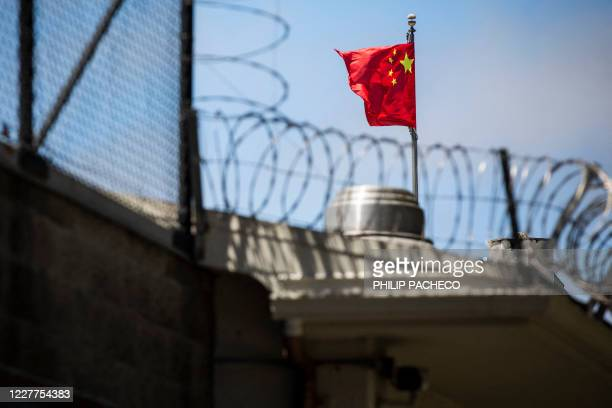 The flag of the People's Republic of China flies behind barbed wire at the Consulate General of the People's Republic of China in San Francisco,...