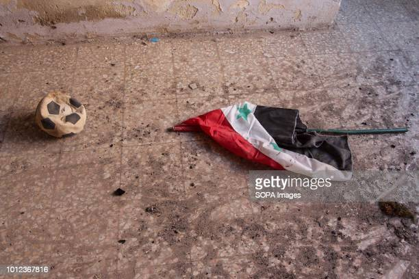 The flag of the Syrian regime appears on the ground next to a child's ball in AlFoah after the government agreed to release 1500 rebel prisoners in...