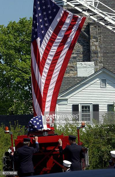 The flagcovered coffin of Firefighter Daniel Harllin rides atop a fire engine outside St James the Apostle Catholc Church in Carmel NY where a...