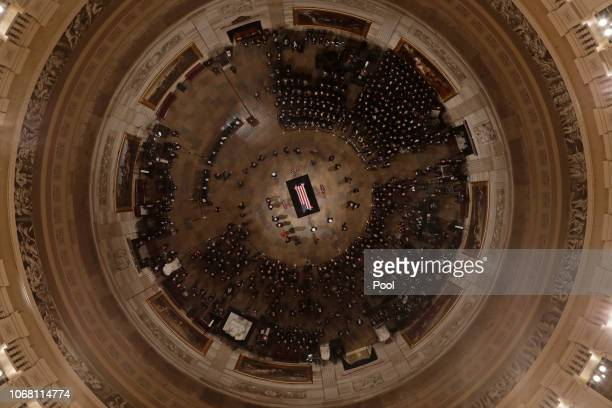 The flag-draped casket containing the remains of Former U.S. President George H. W. Bush lies in state in the U.S. Capitol Rotunda on December 03,...