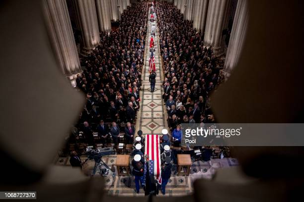 The flagdraped casket of former President George HW Bush is arrives carried by a military honor guard during a State Funeral at the National...