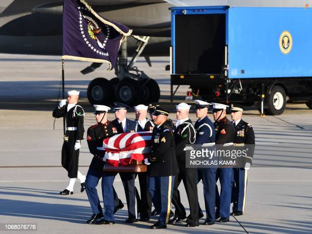 The flagdraped casket of former President George HW Bush is carried by a joint services military honor guard to the hearse at Joint Base Andrews...