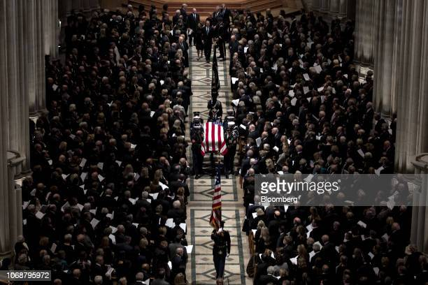 The flagdraped casket of former President George HW Bush is carried out of the National Cathedral following a state funeral service in Washington DC...
