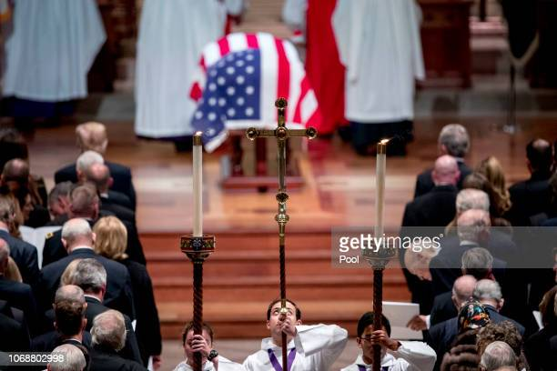 The flagdraped casket of former President George HW Bush is visible as altar servers line up in the center isle during Bush's State Funeral at the...