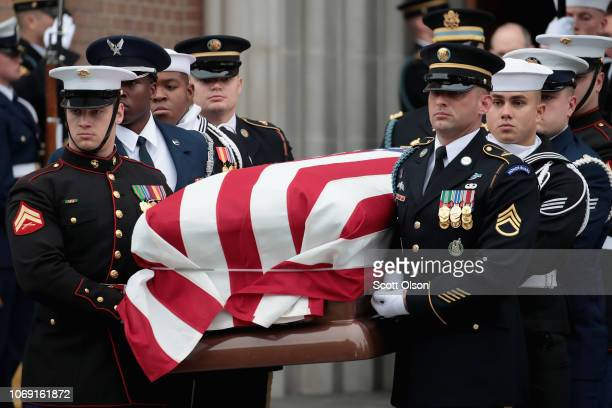 The flagdraped casket of President George HW Bush is carried from St Martin's Episcopal Church following his funeral service December 6 2018 in...