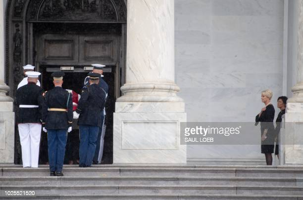 The flagdraped casket of the late US Senator John McCain Republican of Arizona arrives at the US Capitol as his wife looks on in Washington DC August...