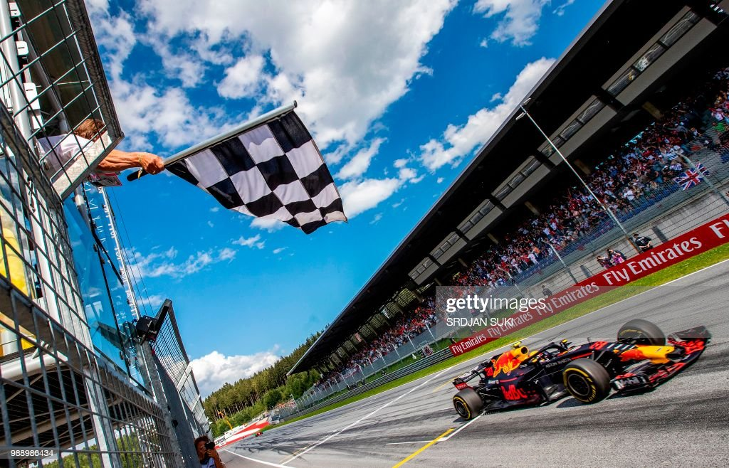 TOPSHOT - The flagman waves the chequered flag as Red Bull's Dutch driver Max Verstappen crosses the finish of the Austrian Formula One Grand Prix in Spielberg, central Austria, on July 1, 2018.