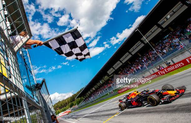 The flagman waves the chequered flag as Red Bull's Dutch driver Max Verstappen crosses the finish of the Austrian Formula One Grand Prix in...