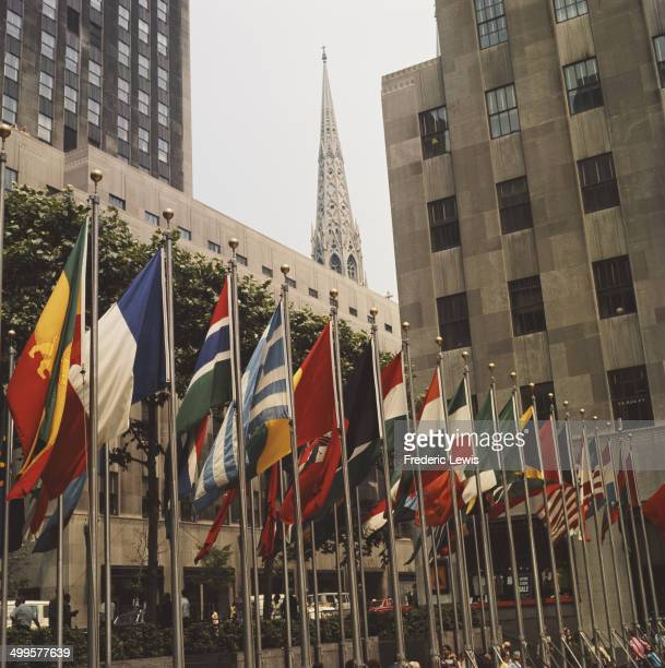 The flags lining Rockefeller Plaza at the Rockefeller Center in New York City USA with the spire of St Patrick's Cathedral visible behind circa 1960