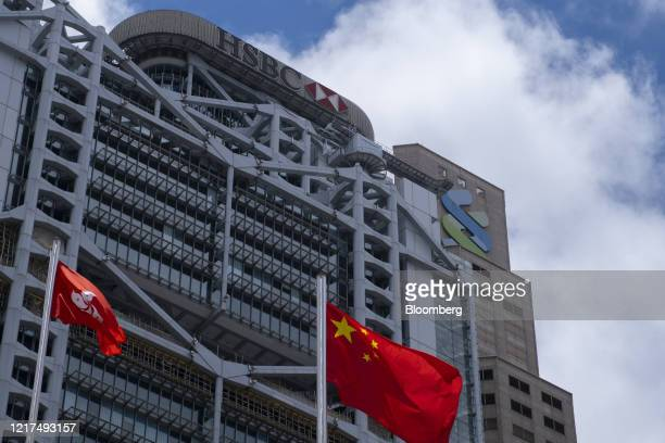 The flags of China and the Hong Kong Special Administrative Region fly near the HSBC Holdings Plc building, left, and the Standard Chartered Plc...