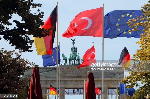 The flags of Germany Turkey and the European Union flutter in front of Berlin's landmark the Brandenburg Gate on September 26 2018 Turkish President...