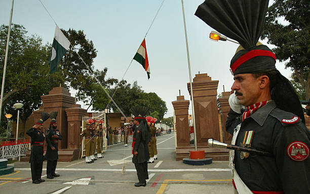 The flags of India and Pakistan are lowered during a ceremony at the border crossing between Pakistan and India March 11 2004 in Wagah Pakistan The...