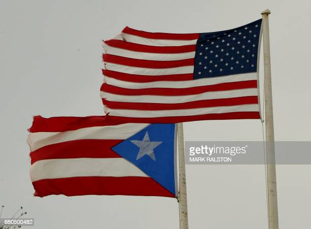 The flags of Puerto Rico and the US fly sidebyside on May 8 2017 in San Juan Puerto Rico as the former Spanish colony of 35 million now a US...
