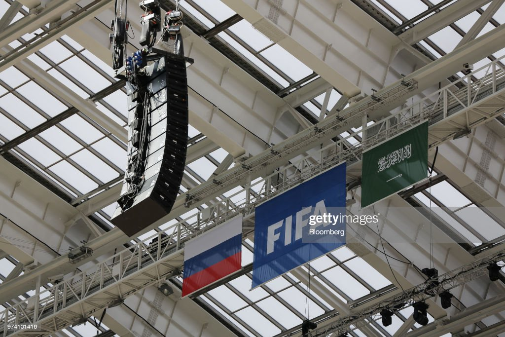 The flags of Russia, left, and Saudi Arabia hang beside a FIFA logo ahead of the FIFA World Cup opening match in the Luzhniki stadium in Moscow, Russia, on Wednesday, June 13, 2018. According to an April report from the organizing committee, the total amount spent on preparations is 683 billion rubles, or about $11 billion at the current exchange rate. Photographer: Andrey Rudakov/Bloomberg via Getty Images