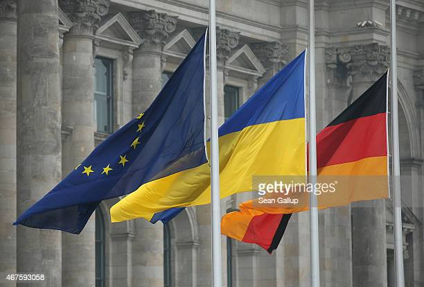The flags of the European Union, Ukraine and Germany fly next to the Reichstag during debates at the Bundestag inside over a European Union...