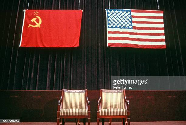 The flags of the USSR and USA hang over chairs on stage at the 1985 Geneva Summit