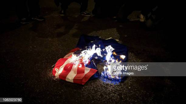 The flags of United States and European Union burns during an antiwar rally in Athens Around one hundred protesters took to the street of Athens to...