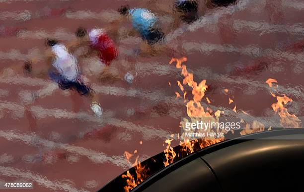 The flame burns as athletes compete in the Men's 110 metres hurdles during day ten of the Baku 2015 European Games at the Olympic Stadium on June 22...