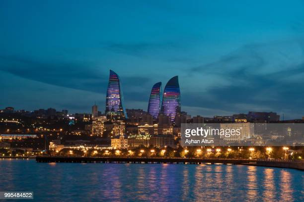 the flame towers and caspian sea  from baku's boulevard park at dusk ,azerbaijan - azerbaijan stock pictures, royalty-free photos & images