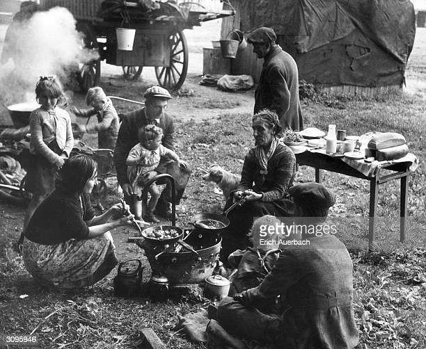 The Fletcher family cook up an evening meal around a makeshift stove in a Buckinghamshire field. The caravan in which they live is pitched nearby.