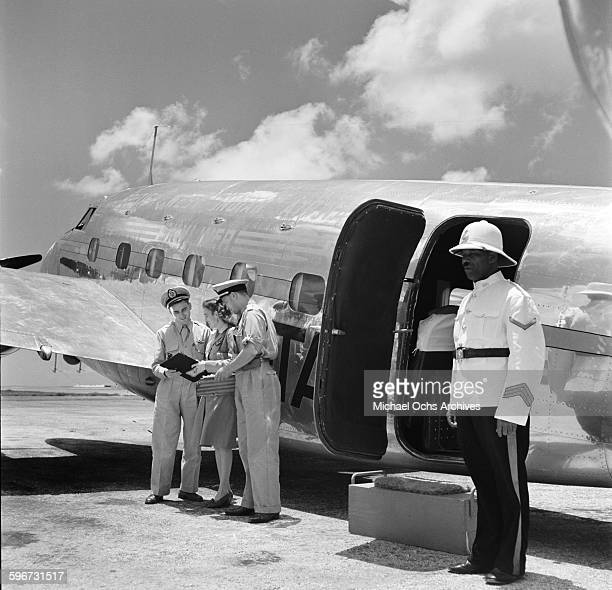 The flight crew looks over the passenger list of the British West Indian Airlines plane at the Piarco International Airport in Piarco Trinidad...