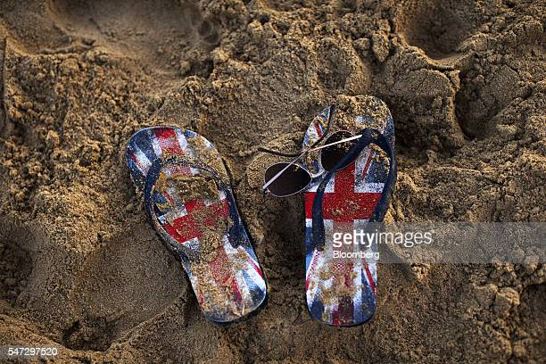 The flip flop sandals of a holidaymaker decorated with the British union flag also known as the Union Jack sit on the sandy beach in Benidorm Spain...