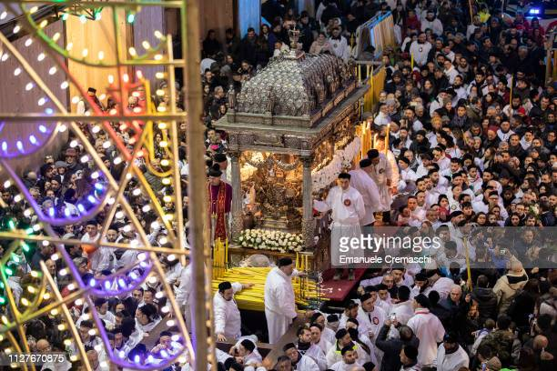 The float containing the relics of Saint Agatha is surrounded by devotees during a night procession on the third day of celebrations of the 'Festa di...