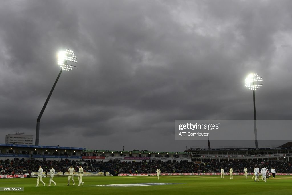 The floodlights are on under stormy skies, as players come off as the rain starts on day 2 of the first Test cricket match between England and the West Indies at Edgbaston in Birmingham, central England on August 18, 2017. / AFP PHOTO / Paul ELLIS / RESTRICTED