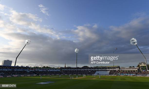 TOPSHOT The floodlights come on as play continues into the evening on the opening day of the first Test cricket match between England and the West...