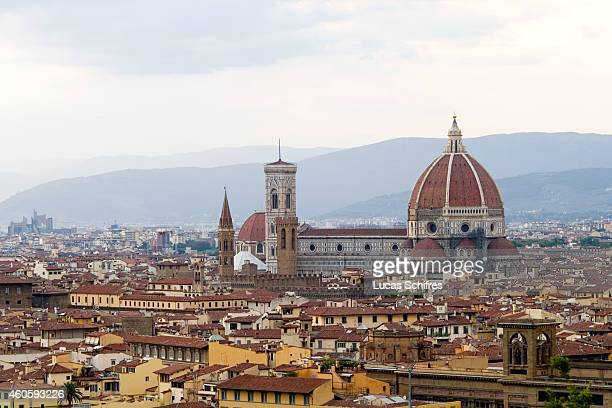 The Florence Cathedral or Basilica of Saint Mary of the Flower stands above the rooves of the city on August 13 in Florence Tuscany Italy Florence...