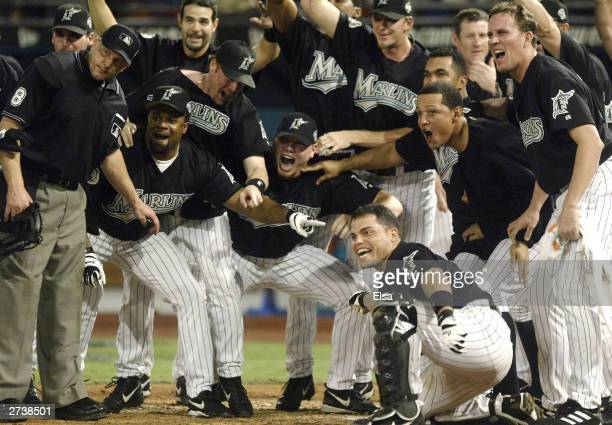 The Florida Marlins await Alex Gonzalez arrival at home plate following his gamewinning solo home run against the New York Yankees in game four of...